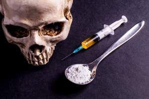 Skull and spray with yellowish liquid. Next to them are a spoon with white powder, which is similar to heroin . Isolated on black